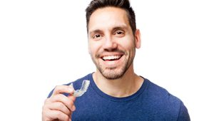 Man holding a clear aligner.