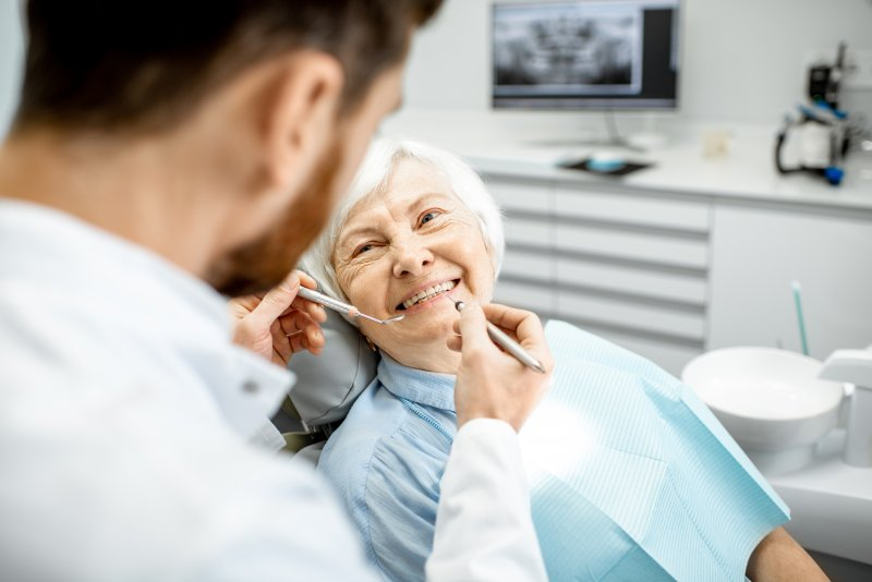 an older woman showing off her new smile while looking at her dentist during a regular visit