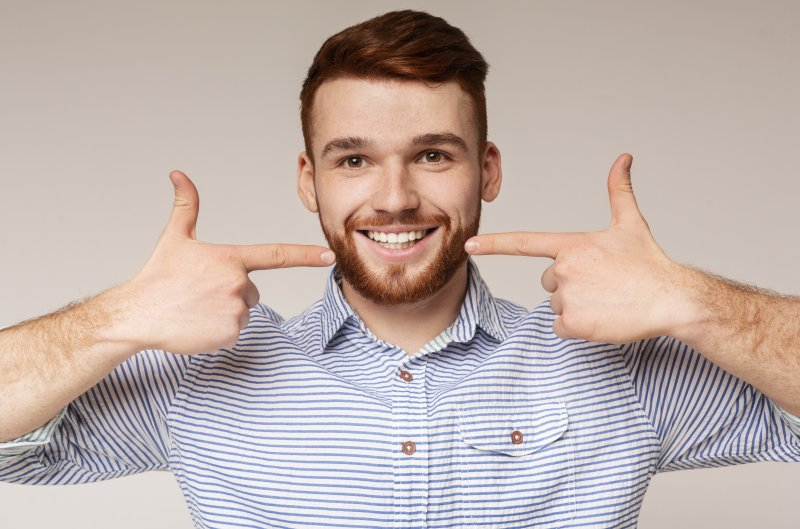 a young man with a beard using both hands to point to his healthy, beautiful smile