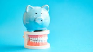 false teeth with a piggy bank indicating the cost of dentures